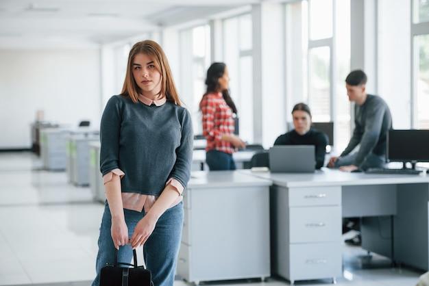 新しいタスクが今日待っています。近代的なオフィスで働くカジュアルな服装の若い人たちのグループ