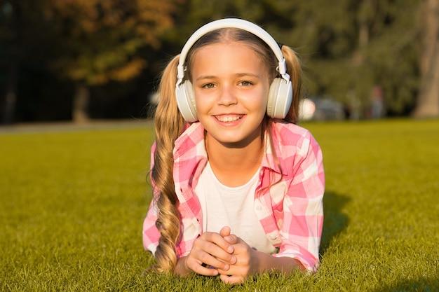 Новые технологии для детей. счастливые детские воспоминания. слушая музыку. обратно в школу. ребенок учится в парке. расслабиться на зеленой траве в наушниках. маленькая девочка слушает аудиокнигу.