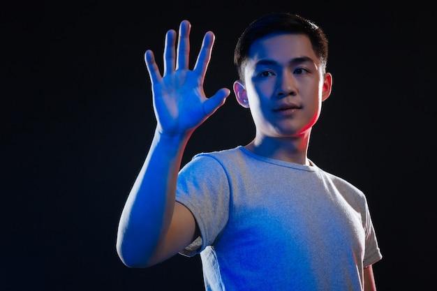 新技術。黒い背景に立っている間彼の手を見て楽しい賢い男