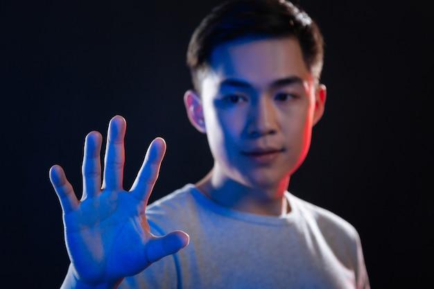 新技術。感覚スクリーンに押し付けられている男性の手のひらの選択的焦点