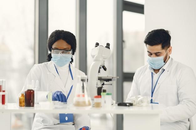 새로운 테스트. 제복을 입은 숙련 된 연구원이 집중. 테스트를하고 백신을 만듭니다.