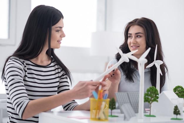 Новое мышление. хорошая позитивная коллега-женщина разговаривает и работает с моделями альтернативной энергетики