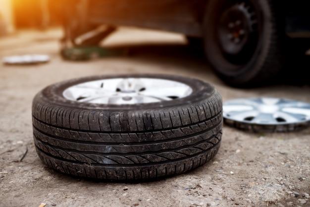 車のタイヤを交換する準備ができている整備士の近くの舗装に敷設された新しいタイヤ。
