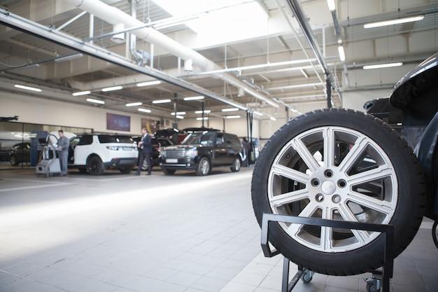 Новые шины на автомобильном колесе в автосервисе, копировальное пространство