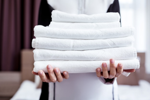 새 수건. 좋은 전문 호텔 메이드의 손에있는 새로운 흰색 수건의 선택적 초점