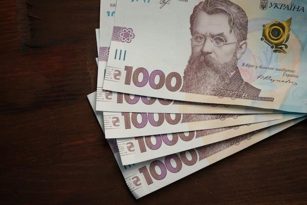 左側のテキストにemty cpaceを使用した木製のテーブルに新しいウクライナの紙幣1000グリブナ額面。ショットを閉じる。ハイアングル