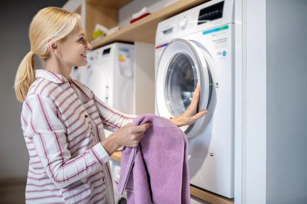 새 세탁기. 세탁기 근처에 서있는 스트라이프 셔츠에 금발 여자