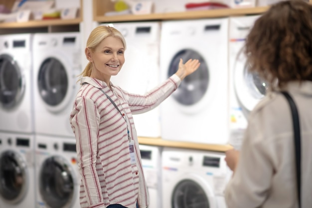 새 세탁기. 고객에게 새 세탁기를 보여주는 스트라이프 셔츠의 영업 도우미