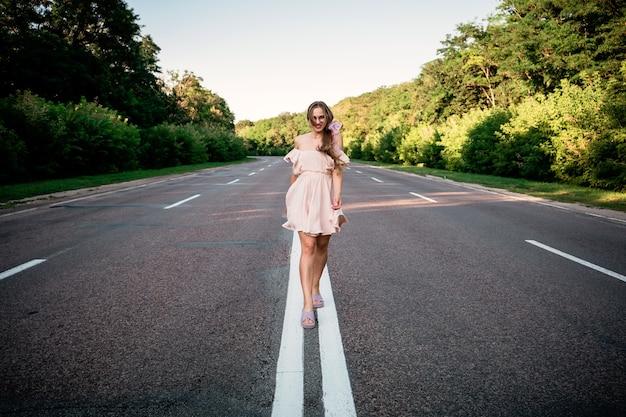 新しい方法、新しいスタート、新年の決議、挑戦、選択または変更の概念。周りの木と夏の道を歩いている若い女性。