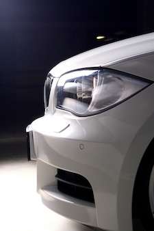 Новый белый автомобиль на черном фоне
