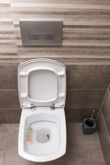 Новый белый керамический туалет на сером фоне плитки. интерьер туалета. современный стиль.