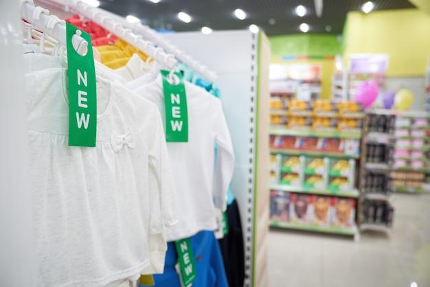 大きな店にぶら下がっている新しい白い子供服