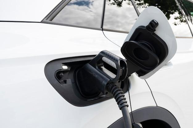 Nuova auto elettrica bianca che si ricarica in una stazione