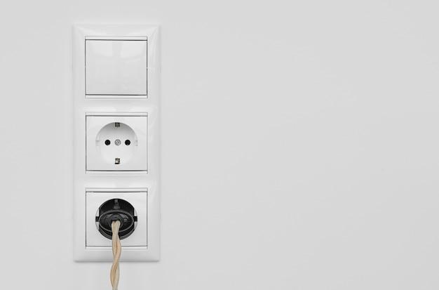 新しい白いプラスチック製のヨーロッパのコンセントとスイッチは、白い漆喰の壁に隔離されています。ヴィンテージケーブル付きの電気プラグがコンセントに差し込まれています。コピースペースのクローズアップ