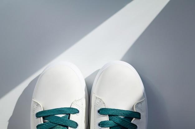 白い背景の上の緑のひもで新しい白いスニーカー