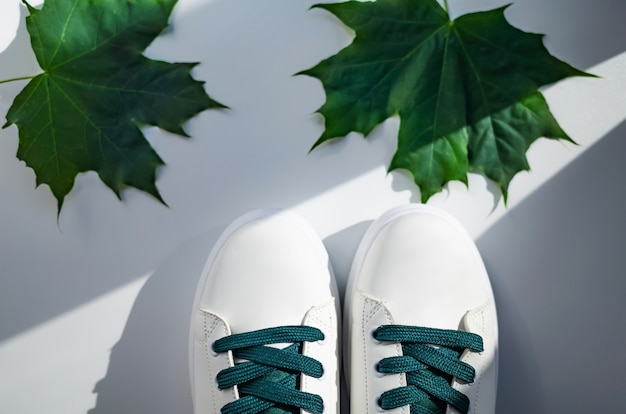New white sneakers with green laces with leaves