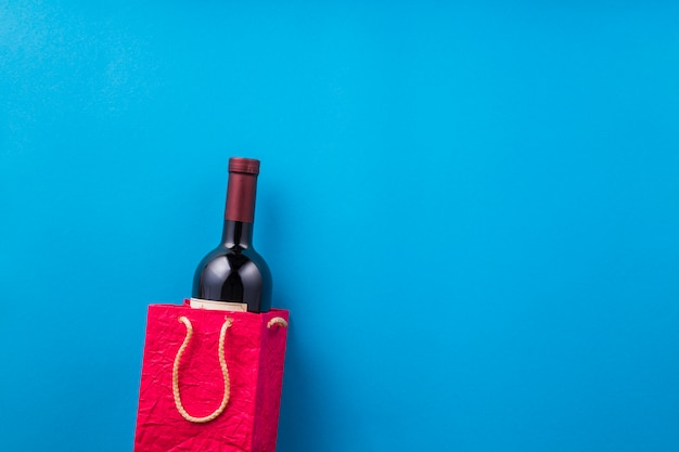 New wine bottle in red paper bag against blue backdrop