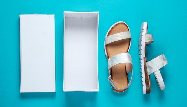 新しい女性の革サンダルと青の空のボックス。開梱。上面図。