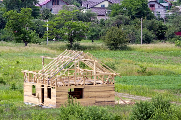 緑の近所で建設中の急な板の屋根フレームを備えた天然木材の新しい木造コテージ。プロパティ、投資、専門的な建物と再建のコンセプト。