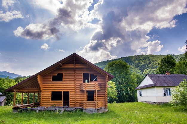 New wooden ecological cottage with balcony, terrace, steep roof from natural materials under construction on grassy meadow on forested hills . old traditions and modern building concept.