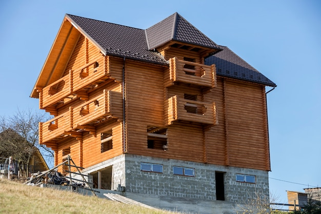 Новый деревянный экологический традиционный коттедж из натуральных пиломатериалов с черепичной крышей и каменным подвалом в стадии строительства в зеленом районе на фоне голубого неба.