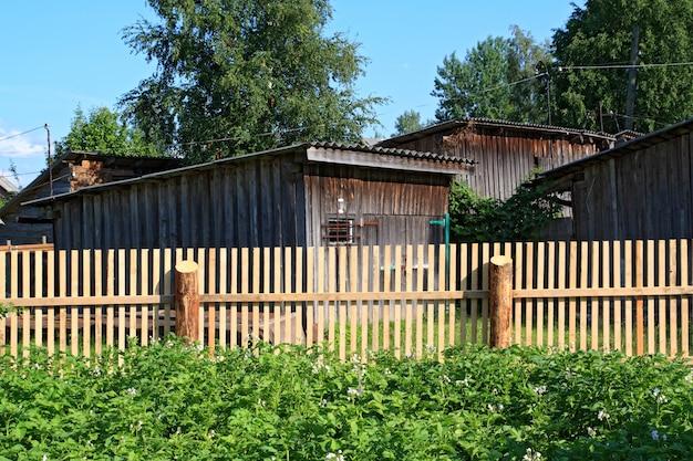 農村の菜園で新しい木製のフェンス