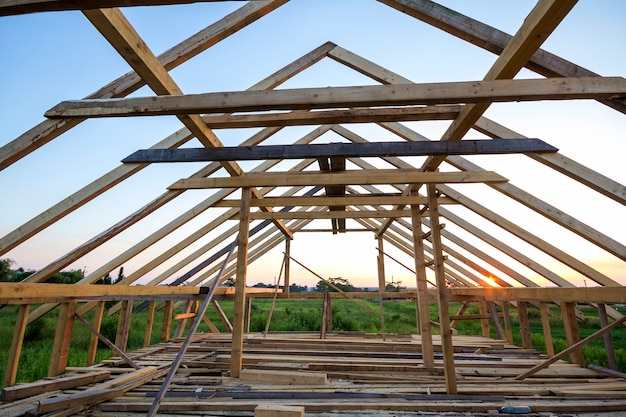 建設中の新しい木造住宅。内側から澄んだ空を背景に屋根裏部屋の屋根フレームのクローズアップ。
