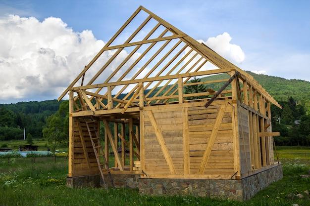 静かな農村地域で建設中の新しい木造住宅。石造りの基礎の壁および屋根用の天然素材の木材フレーム。プロパティ、プロの建物および再建のコンセプト。