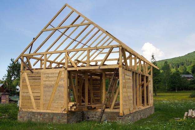 Новый деревянный дом в стадии строительства в тихом сельском районе. деревянный каркас из натуральных материалов для стен и кровли на каменном фундаменте. собственность, профессиональная концепция строительства и реконструкции.