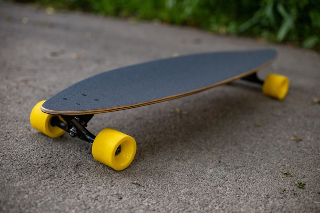 New wooden penny board with yellow wheels on the asphalt