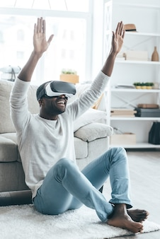 New word of virtual reality!  handsome young african man in vr headset gesturing and smiling while sitting on the carpet at home