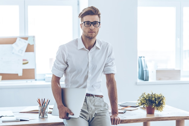 新しい営業日。ノートパソコンを保持し、オフィスのテーブルに寄りかかってカメラを見ている眼鏡のハンサムな若い男