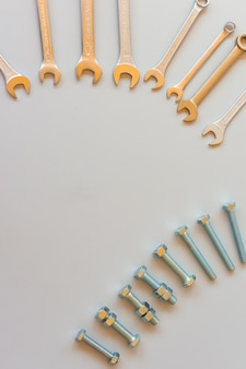 New wrenches on grey background, top view with space for text. professional plumber tools with fixing bolts.