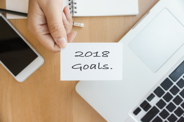 New year 2018 - closeup top view photo woman showing 2018 goal list on business card and using modern laptop and mobile phone on wood table blurred background.
