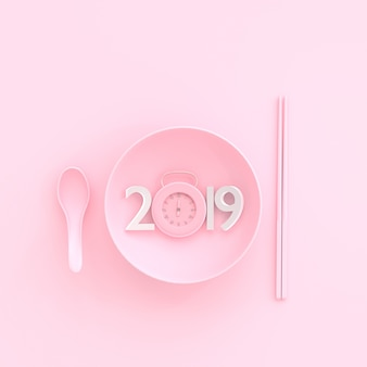 New year 2019 concept and clock pink pastel color in bowl with spoon and chopsticks.