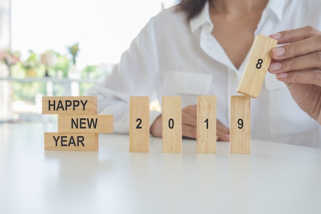New year 2019 concept. young woman building 2019 concept with wooden blocks.