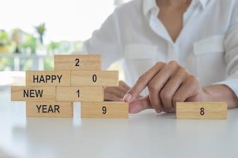 Новый год 2019 концепция. Молодая женщина строя концепцию 2019 с деревянными блоками.