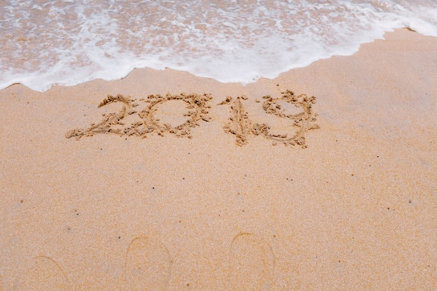 New year 2019 is coming concept and 2018 is been erasing by wave on sand beach background
