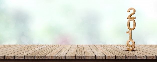 New year 2019 on wooden table at blur abstract green bokeh background