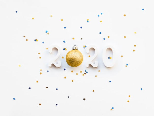 New year 2020 background with golden ball and star confetti.