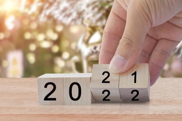 Новый год 2020 меняется на 2021 год. переверните руку над деревянным кубиком. концепция новогоднего праздника