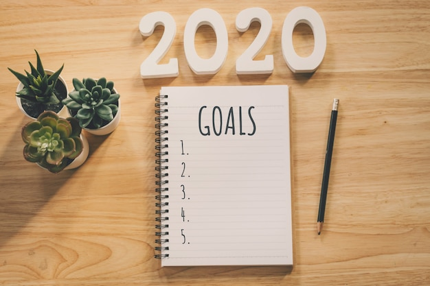New year 2020 goals list. office desk table with notebooks and pancil with pot plant.