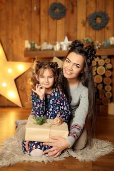 新年2020。メリークリスマス、幸せな休日。母とギフトボックスを持つ少女のクローズアップの肖像画。夜のクリスマスツリーのインテリアの魔法の光