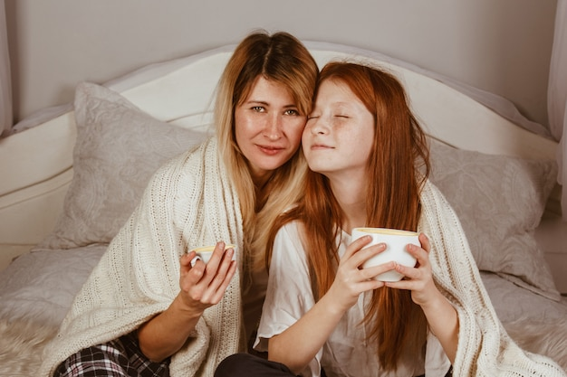New year 2020. mom and ginger-haired daughter are sitting on the bed and drinking cocoa with froth. covered with a blanket, hug.