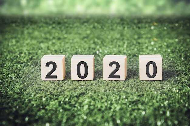 New year 2020 on wooden cubes with green background.
