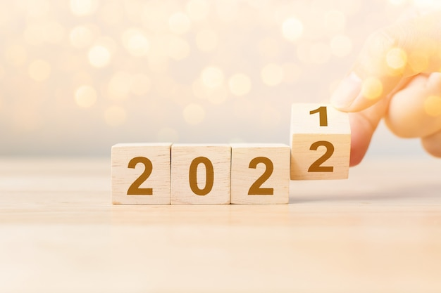 New year 2021 change to 2022 concept hand flip over wood cube block on wooden table