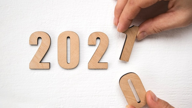 New year 2021 concept with hand putting wooden numbers 2021 on wooden table