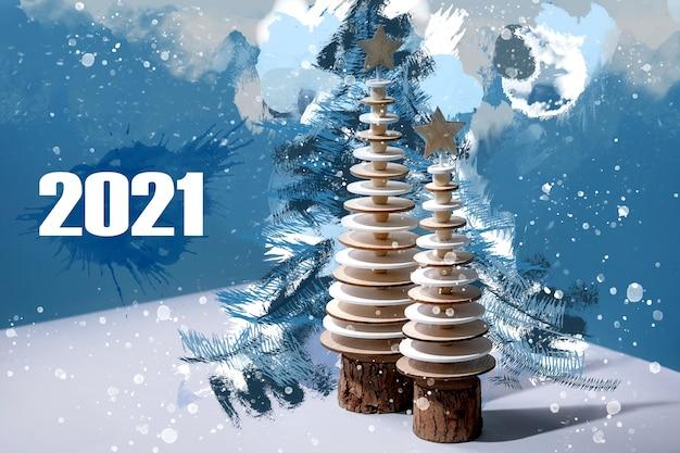 Новогодняя поздравительная открытка 2021 года с современными рождественскими украшениями, деревянными елями и акварельными креативными элементами над синим.