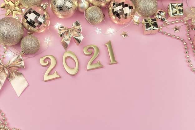New year 2021 golden numbers in the design of the golden christmas decor on a pink background.
