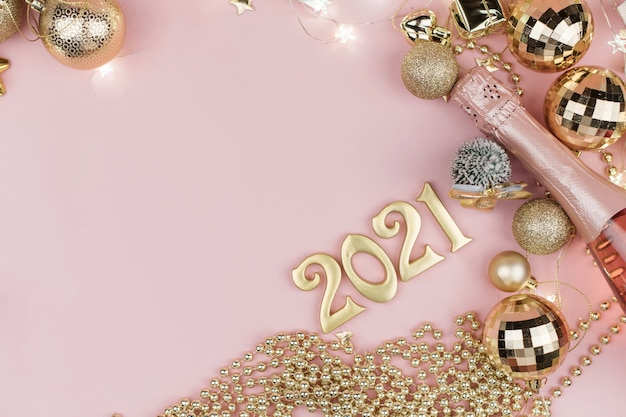 New year 2021 golden numbers in the design of the golden christmas decor on a pink.